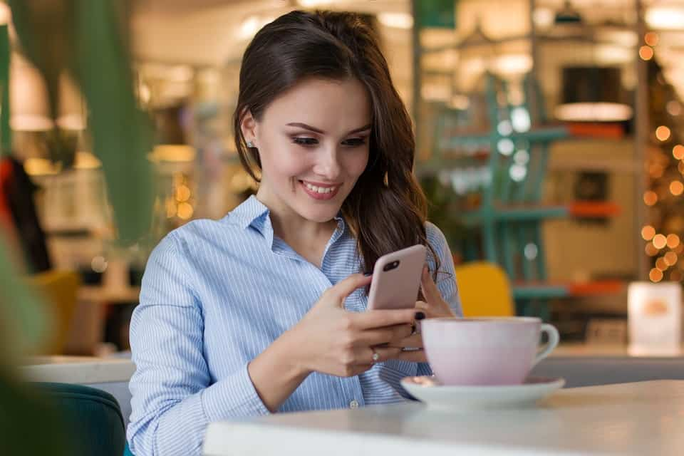 woman smiling while checking her phone